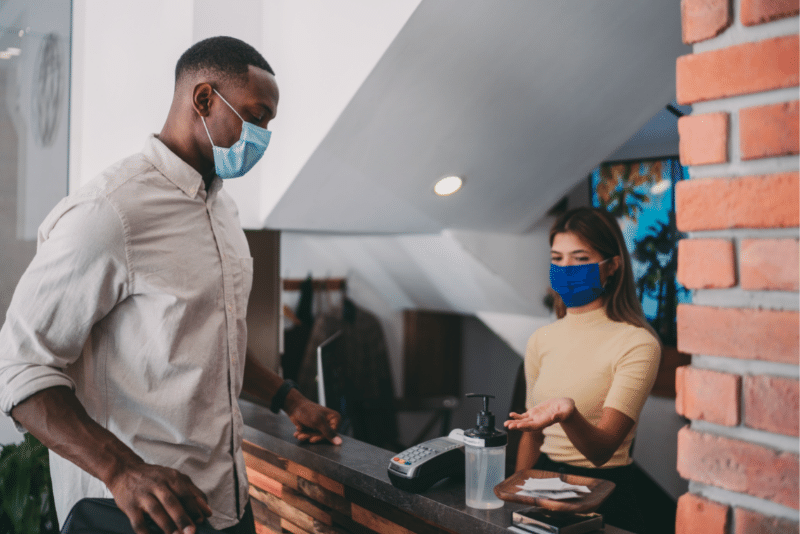 man checking into hotel wearing PPE mask