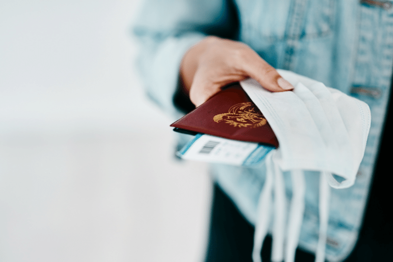 Woman's hand holding a foreign passport, ticket, and PPE Mask
